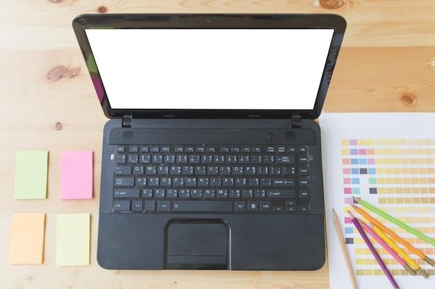 Grafische design bureautafel met computer, plaknotities en kleurengidspaletstalen