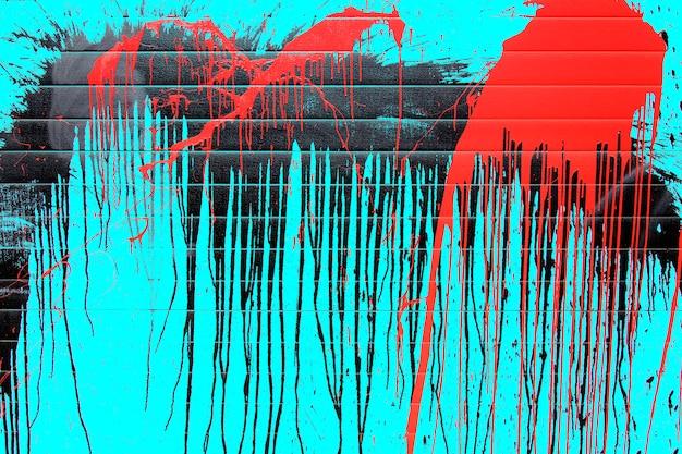 Grafische druppels rode en zwarte verf op een blauwe achtergrond.