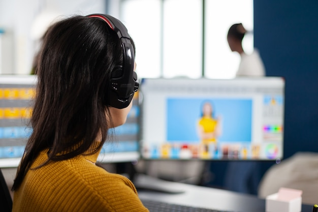 Grafische editor die foto's van een klant retoucheert op een prestatie-pc met twee beeldschermen setup