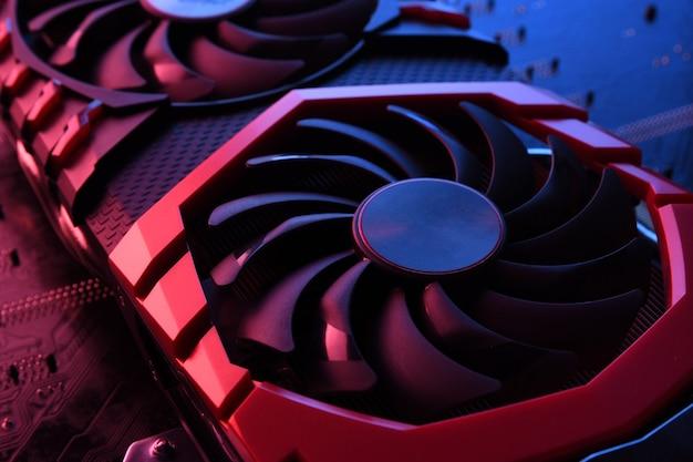 Grafische kaart van computerspel, videokaart met twee koelers op printplaat. close-up. met rood-blauwe verlichting.