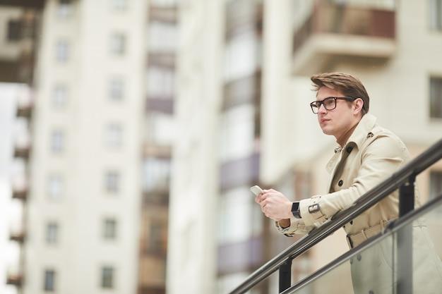 Grafische lage hoek portret van moderne jonge zakenman dragen trenchcoat en smartphone houden terwijl leunend op reling buitenshuis in stedelijke stad omgeving, kopie ruimte