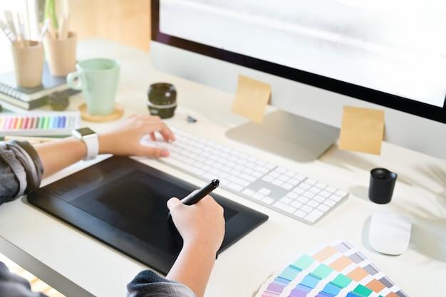 Grafische ontwerper die aan digitale tablet werkt.