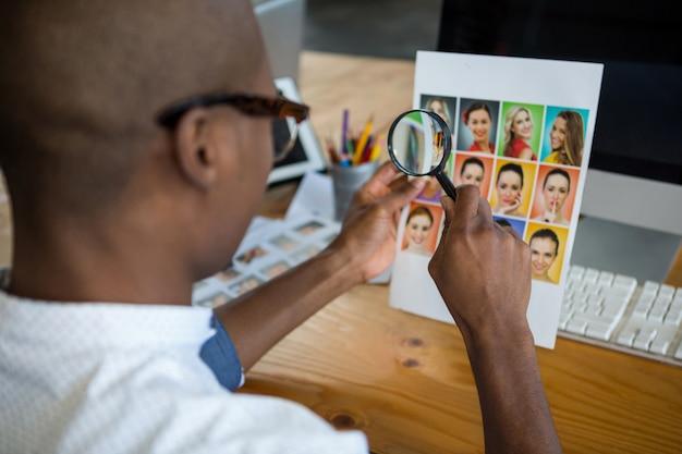 Grafische ontwerper die foto met vergrootglas bij bureau bekijkt