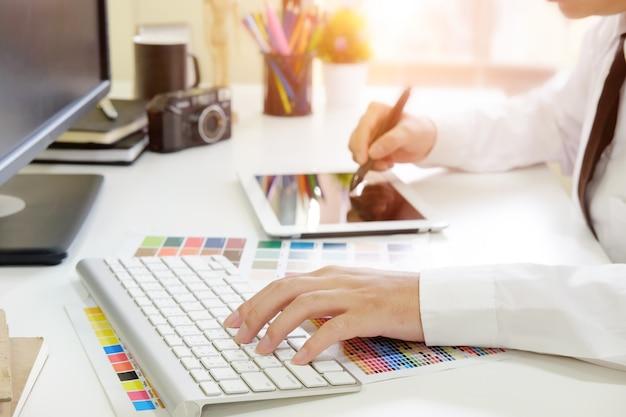 Grafische ontwerper die met digitale tablet bebouwde geschotene foto werkt.