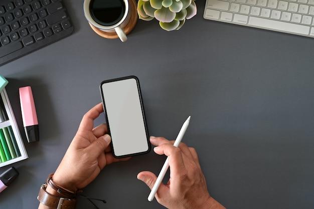 Grafische ontwerper die mobiele slimme telefoon op studio hoogste lijst houdt
