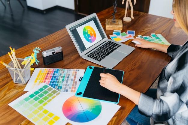 Grafische ontwerper met laptop en grafische tablet