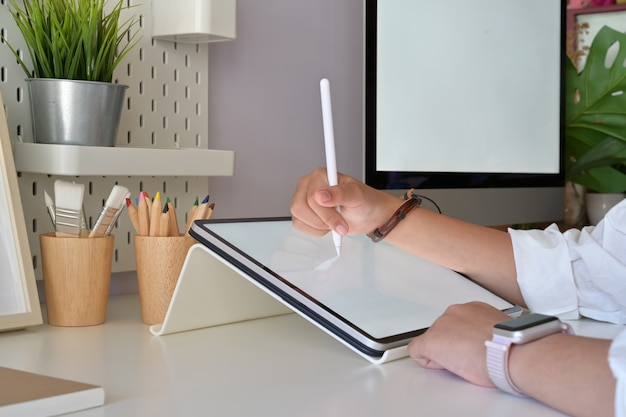 Grafische ontwerperhand die digitale de tabletpen van de tekeningschets in studio gebruiken