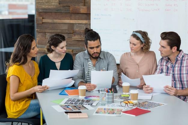Grafische ontwerpers bespreken over document in vergadering