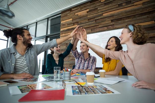 Grafische ontwerpers geven high five tijdens meeting