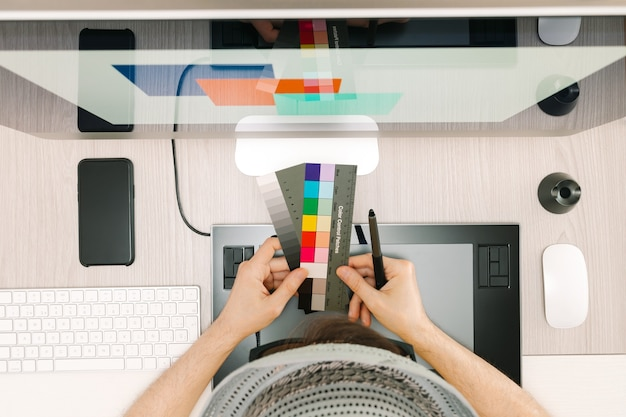 Grafische retoucher die kleurstalen kiest uit patches voor het scherm met een digitale pen in de hand met een pet en een bril