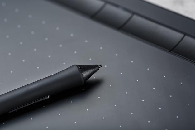 Grafische tablet met een pen werkende ontwerper, close-up. gadget voor creativiteit en werk van een fotograaf, illustrator en kunstkunstenaar.