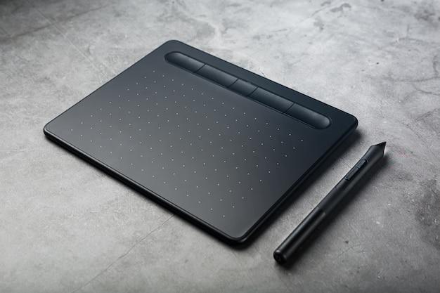Grafische tablet met een stylus op een donkere weefsel achtergrond, bovenaanzicht. gadget om te werken als ontwerper, kunstenaar en fotograaf