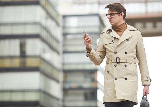 Grafische taille portret van moderne jonge zakenman dragen trenchcoat en smartphone houden lopen naar camera terwijl woon-werkverkeer in stedelijke stad omgeving, kopie ruimte