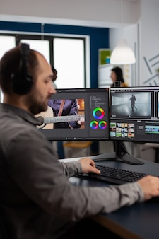Grafische videoproductie die op pc werkt met twee schermen die video- en audiobeelden bewerken op een creatieve werkplek