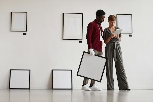 Grafische volledige lengte portret van vrouwelijke art gallery manager met behulp van digitale tablet tijdens het instrueren van assistent en planning van tentoonstelling in museum,