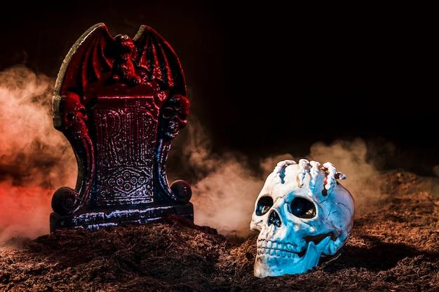 Grafsteen en schedel tussen mist op grond