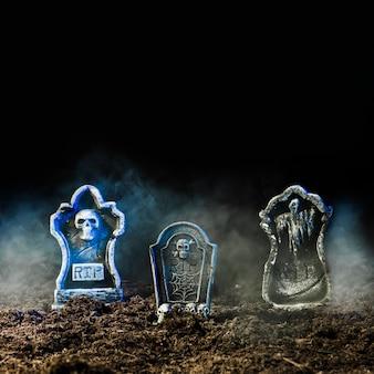 Grafstenen in mist op grond