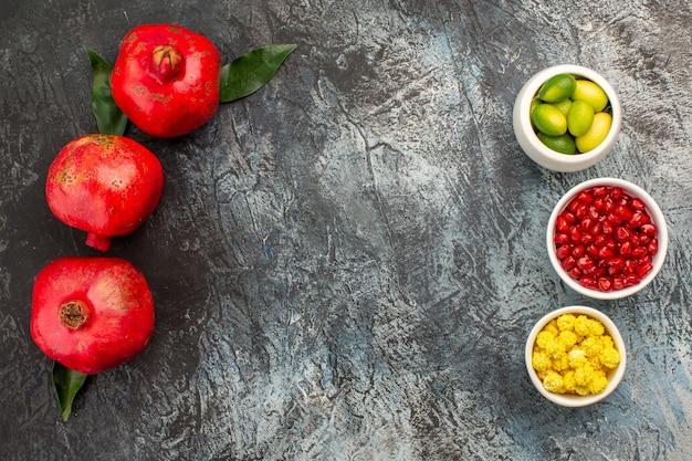 Granaatappel drie granaatappels met bladeren en kommen met bessen citrusvruchten