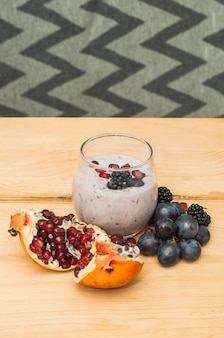 Granaatappel; druiven en frambozen smoothies op houten tafel tegen behang