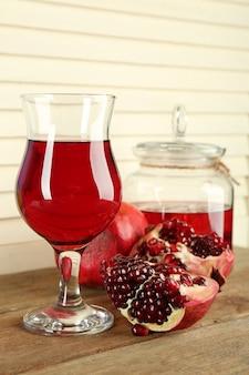 Granaatappel en glas sap op houten tafel en wight hek