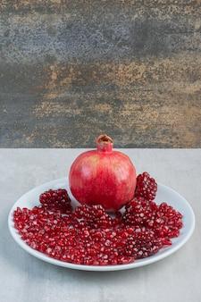 Granaatappel en granaatappelzaden op witte plaat. hoge kwaliteit foto