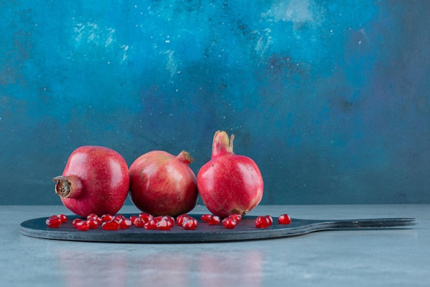 Granaatappel en rode zaden op een zwarte schotel.