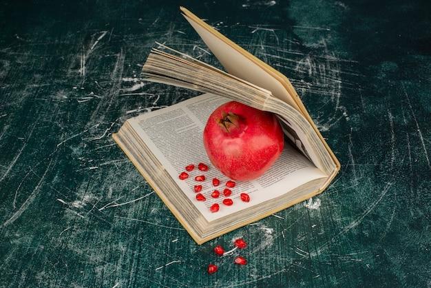 Granaatappel in een boek op marmeren oppervlak.