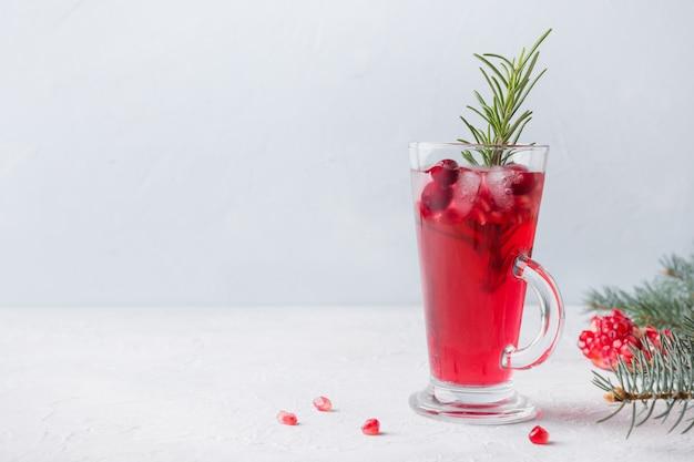 Granaatappel kerstcocktail met rozemarijn, champagne, sodawater op grijze concrete lijst.