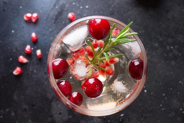 Granaatappel kerstcocktail met rozemarijn, sodawater op zwarte tafel. detailopname. uitzicht van boven.