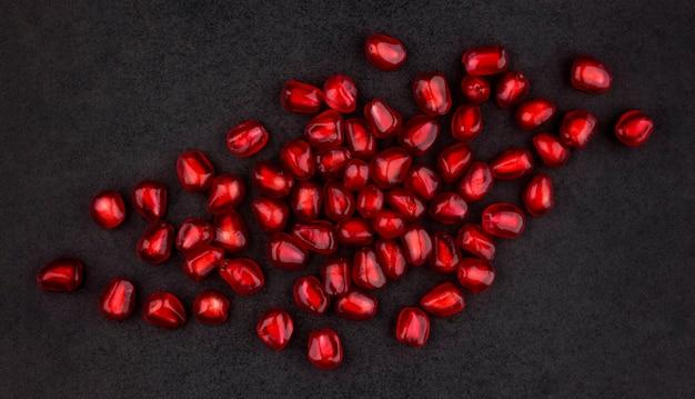 Granaatappel zaden op zwart oppervlak, met lege ruimte voor tekst