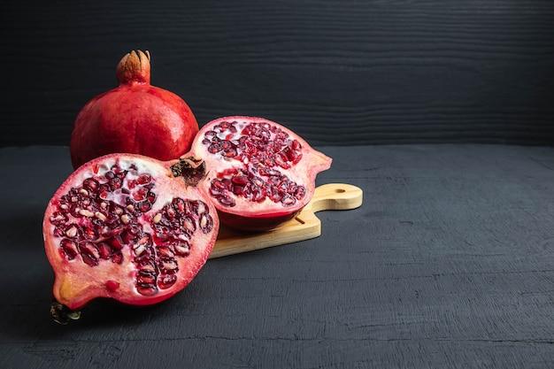 Granaatappelfruit op zwarte achtergrond wordt gesneden die