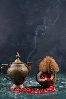 Granaatappelpitjes in kokos en theepot op marmeren tafel.