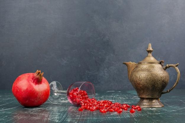 Granaatappelpitjes verspreid over marmeren tafel met theepot.