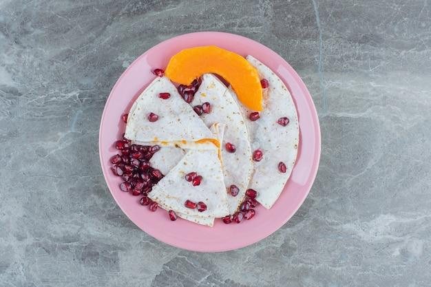 Granaatappelpitten en gesneden pompoen met lavash op plaat, op de marmeren tafel.
