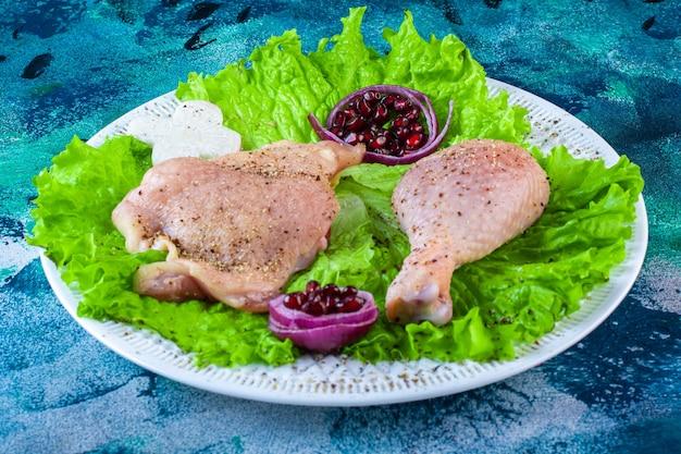 Granaatappelpitten, slablaadjes met uienring naast kippenvlees op een bord