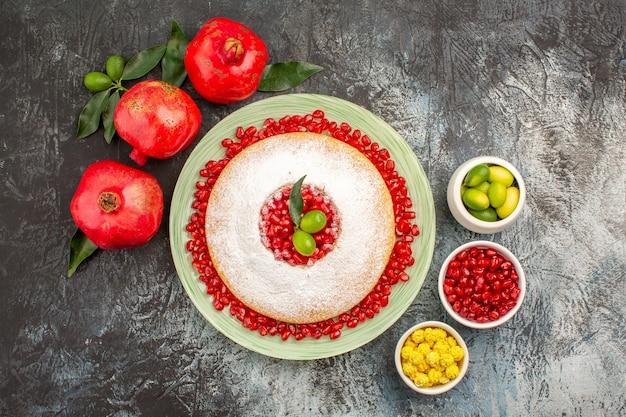 Granaatappels drie smakelijke granaatappels een bord cake en schalen met bessen