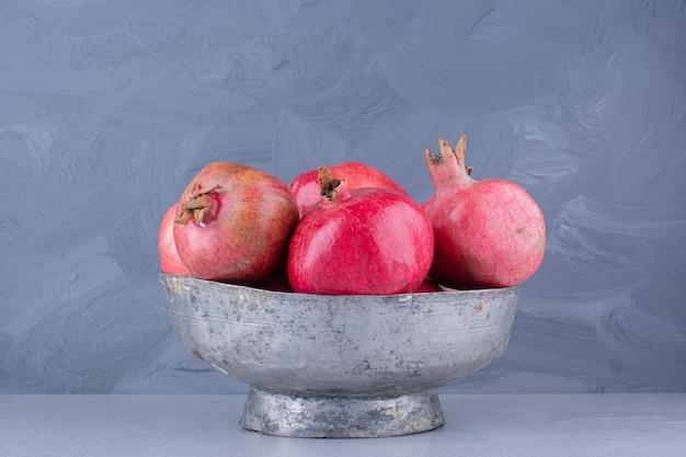 Granaatappels in een metalen vaas op marmeren achtergrond.