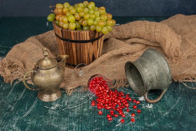 Granaatappelzaden en emmer druiven op marmeren tafel met vaas en theepot