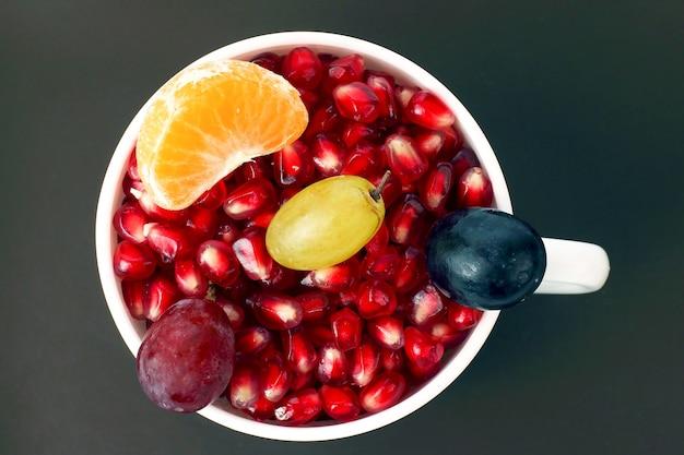 Granaatappelzaden en fruit in een witte kop op een donkere achtergrond. vitamine voedsel