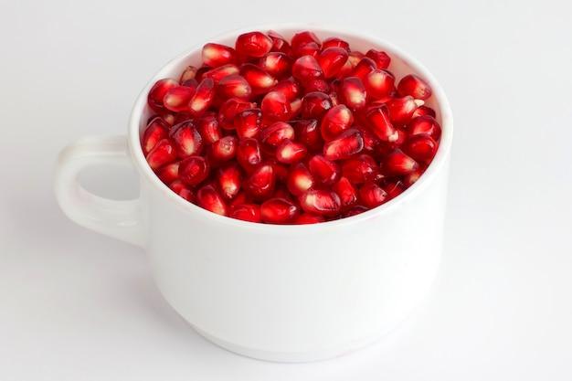 Granaatappelzaden in een witte kop op een witte achtergrond. vitamine voedsel
