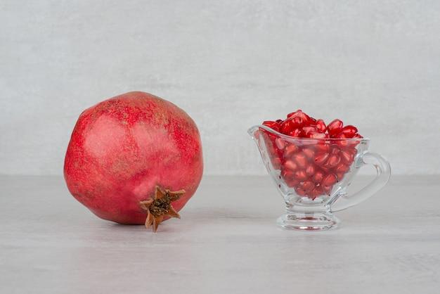 Granaatappelzaden in glas en granaatappel op wit.