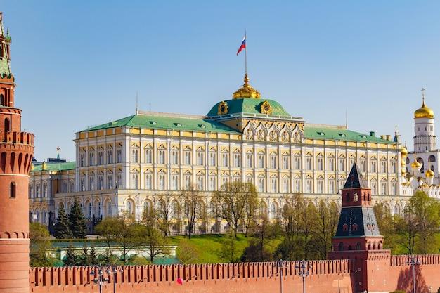 Grand kremlin palace van het kremlin van moskou met russische vlag zwaaien tegen blauwe hemel