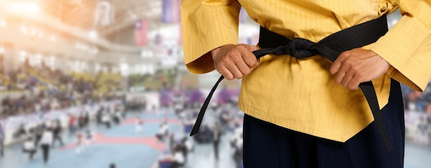 Grand master black belt taekwondo leraar houdt vast en stropdas riem pose, taille deel studio over international competition stadion zone als achtergrond