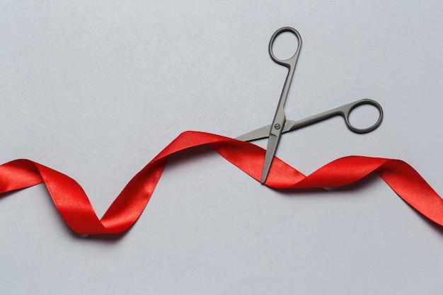 Grand opening geïllustreerd met een schaar en een rood lint op een grijze