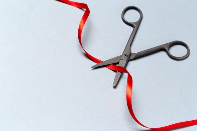 Grand opening geïllustreerd met een schaar en een rood lint