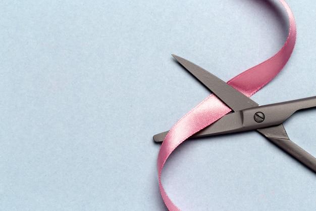 Grand opening geïllustreerd met een schaar en een roze lint