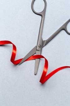 Grand opening met een schaar en een rood lint op een grijze achtergrond