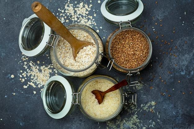 Granen (havermout, boekweit, rijst) in glazen potten in de keuken. glutenvrij concept. soorten granen voor het maken van gezonde zelfgemaakte gerechten en maaltijden.