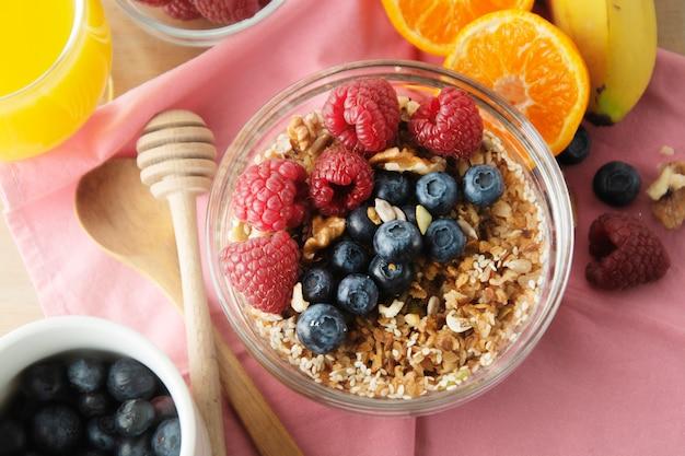 Granen met fruit, bessen als ontbijt. gezond ontbijt, roze achtergrond.