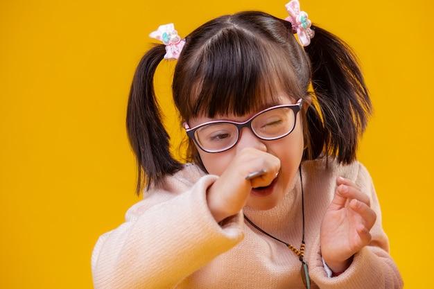 Granen met melk. buitengewoon meisje met het syndroom van down met ongebruikelijke gezichtskenmerken die maaltijd eten met een metalen lepel
